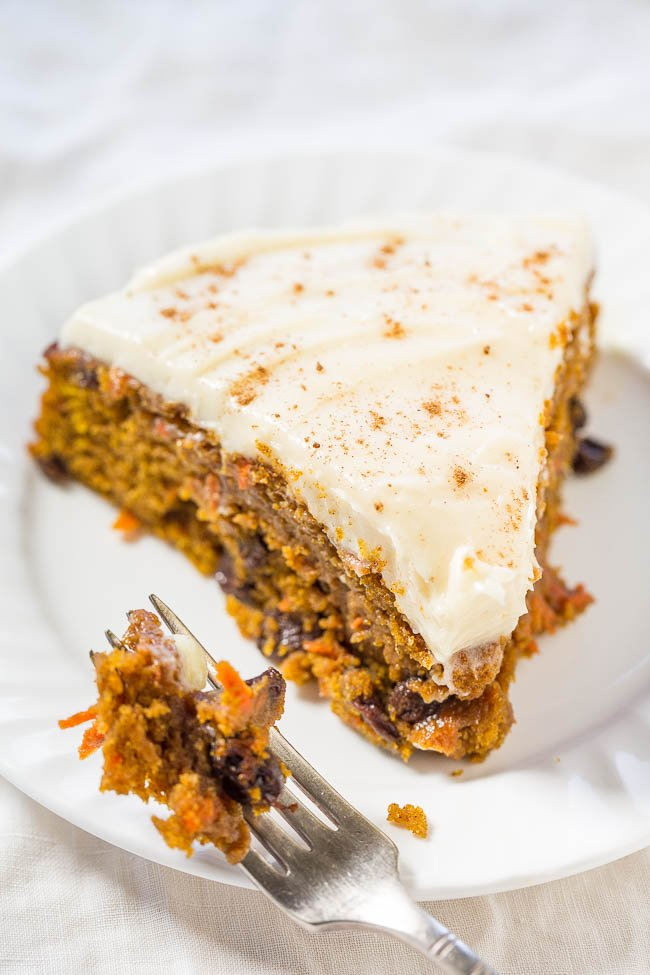 a slice of frosted pumpkin carrot cake on a white plate with a fork