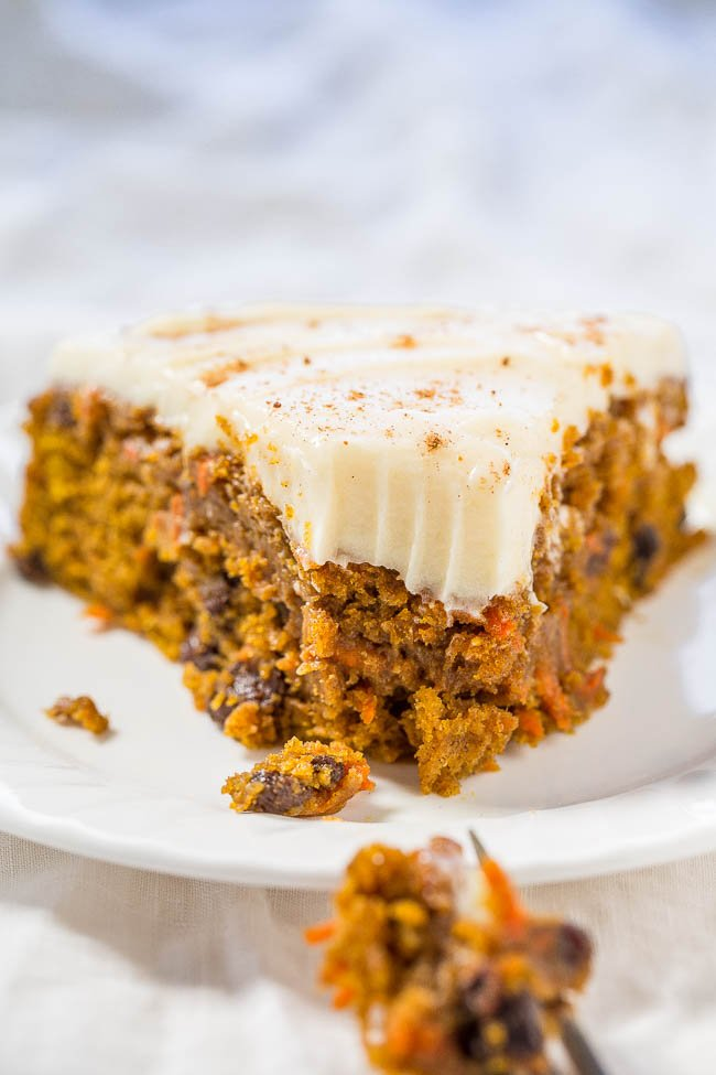 a slice of frosted pumpkin carrot cake with a bite missing on a white plate