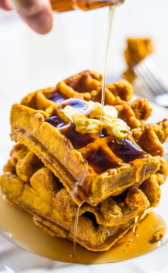 maple syrup being drizzled onto a stack of Pumpkin Waffles