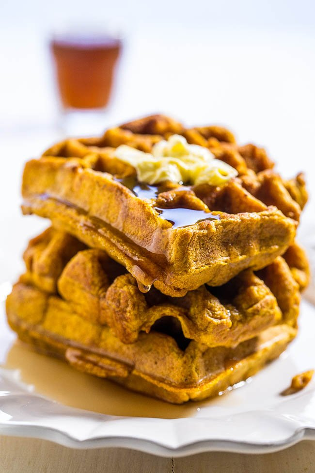 stack of Pumpkin Waffles with maple syrup and butter on top