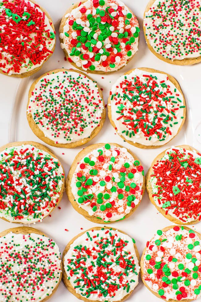 overhead view of soft frosted sugar cookies on a platter. Each cookie has been topped with green and red sprinkles.