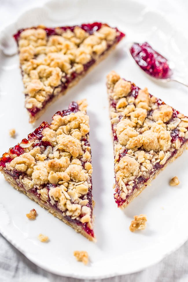 three raspberry bars on a white plate