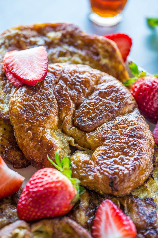 close up view of croissant french toast on a white platter with berries