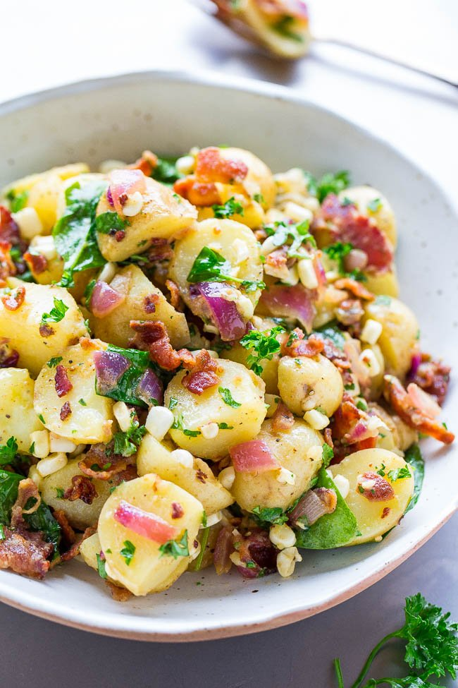german potato salad with bacon in large white serving bowl