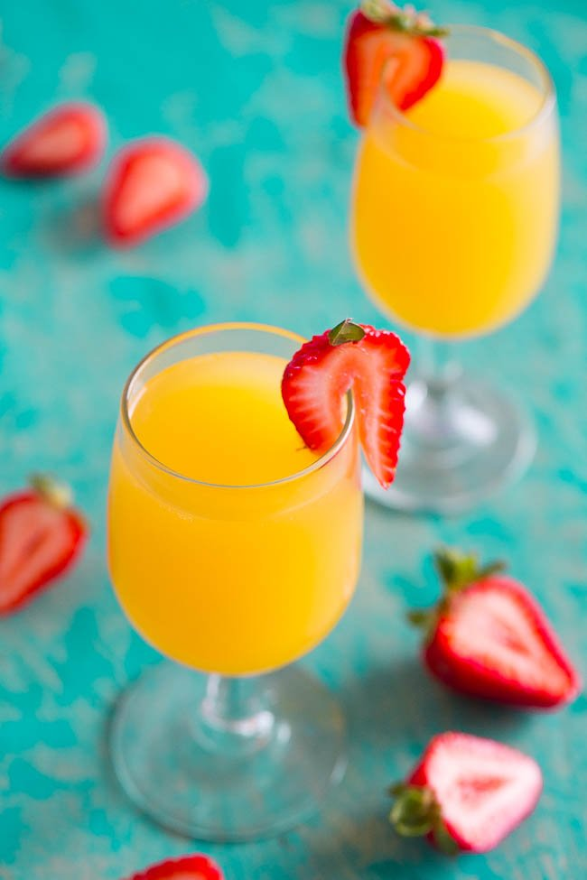 overhead view of two mimosa drinks garnished with strawberry slices