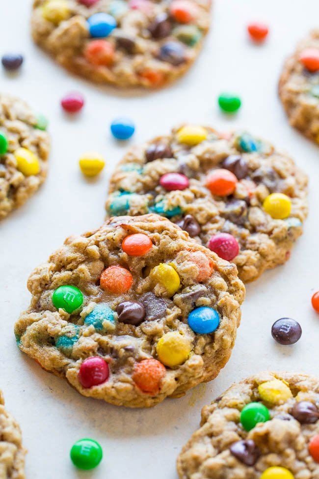 six chocolate chip oatmeal m&m cookies on countertop surrounded by M&Ms