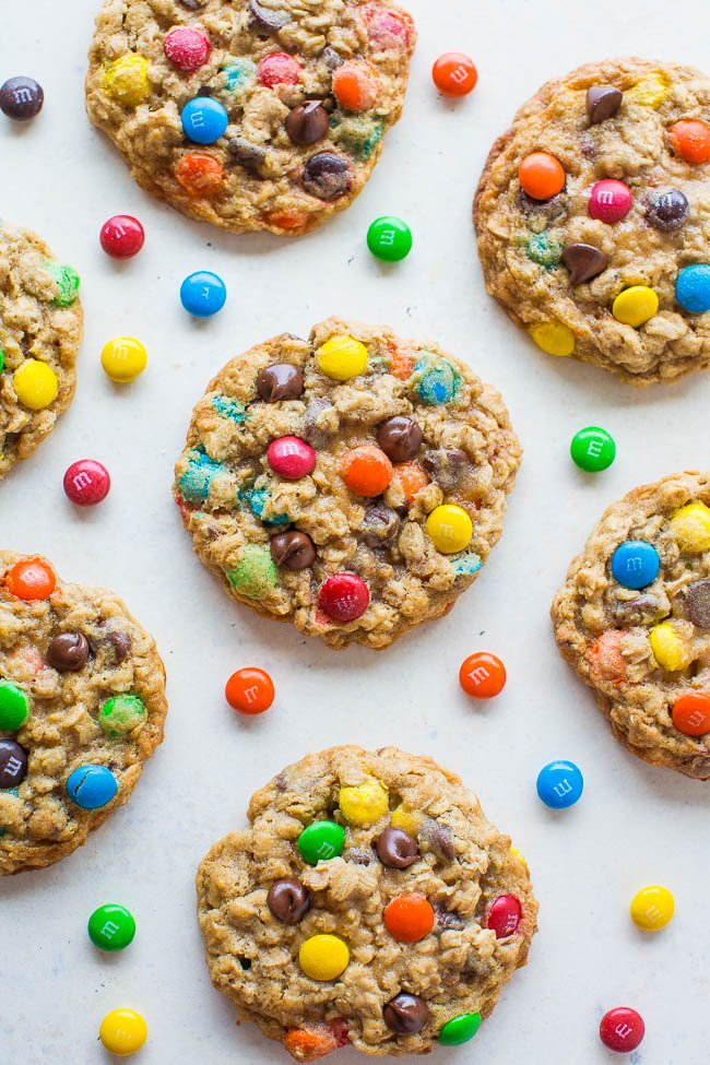 overhead view of seven oatmeal m&m cookies on countertop surrounded by M&Ms