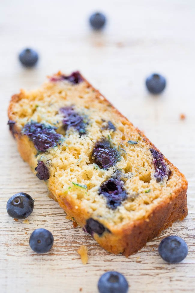 slice of Blueberry Zucchini Bread on counter surrounded by fresh blueberries