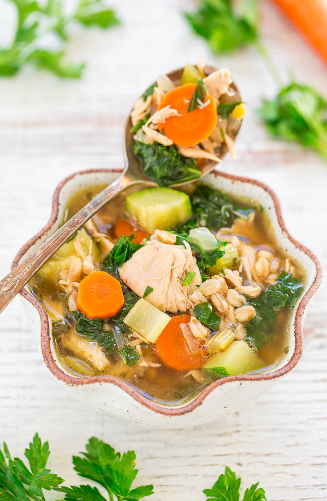 a bowl of chicken vegetable soup with a spoon resting on the edge
