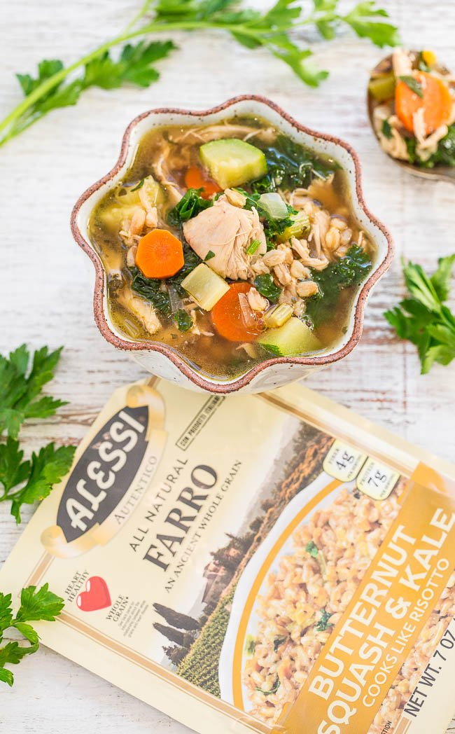 overhead view of a bowl of chicken vegetable soup next to a packet of farro