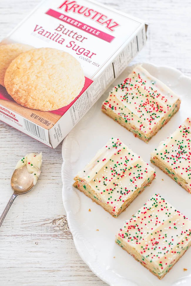 four Christmas sugar cookie bars on a white platter next to a box of Krusteaz cookie mix