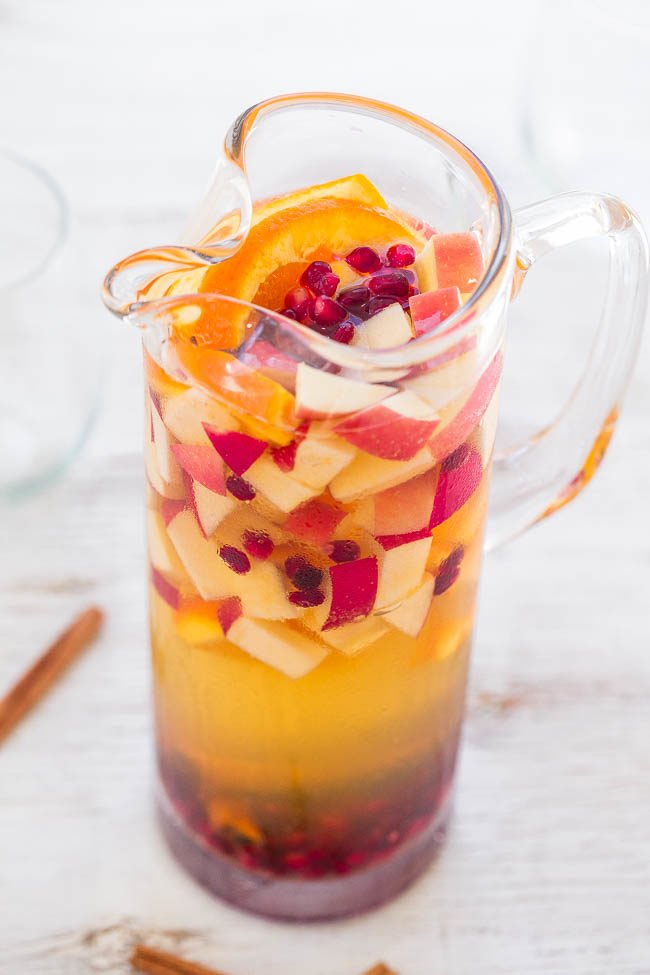 Sparkling Apple Cider Sangria - Apples, oranges, pomegranate seeds, and cinnamon sticks with sparkling cider are a FUN twist on classic sangria!! So easy! Make it for your next party and everyone will want a refill!!