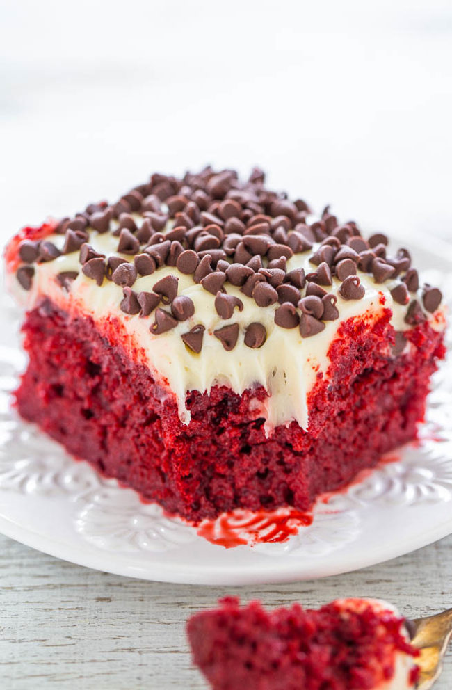 Red Velvet Poke Cake with Cream Cheese Frosting on a white plate