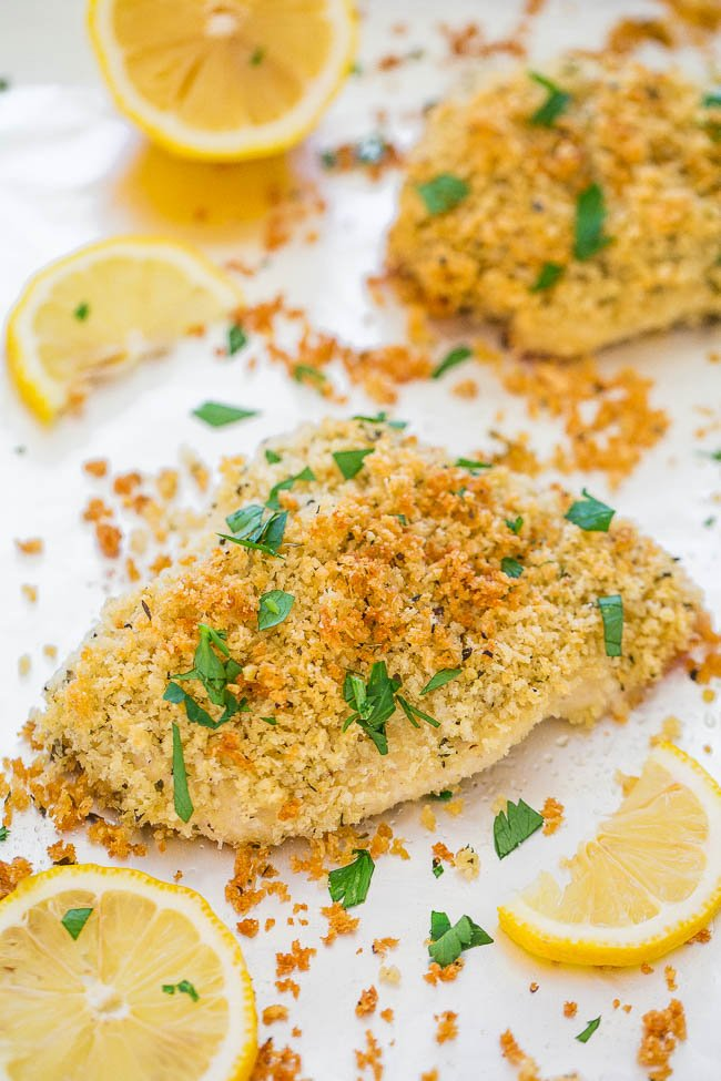 Baked Parmesan Crusted Chicken garnished with parsley and lemon wedges