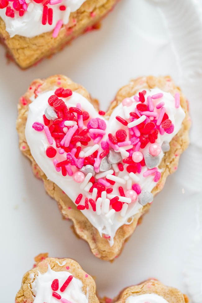 Soft Frosted Valentine Heart Cookies - The EASIEST cutout cookies you'll ever make!! No rolling pin, no mixer, no chilling the dough! Soft and chewy with plenty of frosting and sprinkles!!