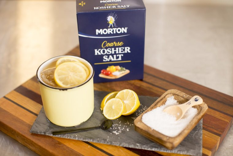 Morton's salt on a white plate a cutting board with lemon slices