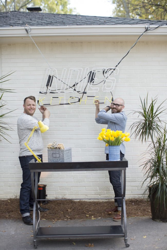 Two men hanging a sign in the backyard next to a table with yellow flowers