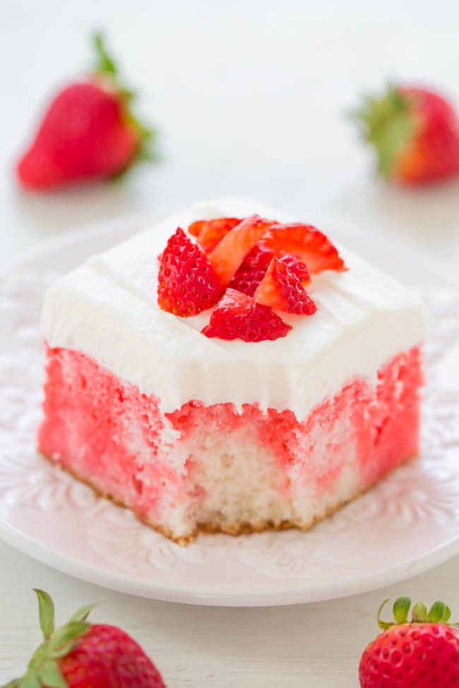 Strawberries and cream poke cake on a white plate