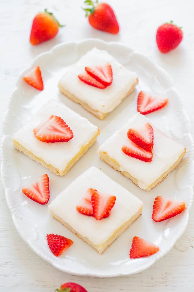 four Strawberry Shortbread Bars on white platter surrounded by fresh strawberries