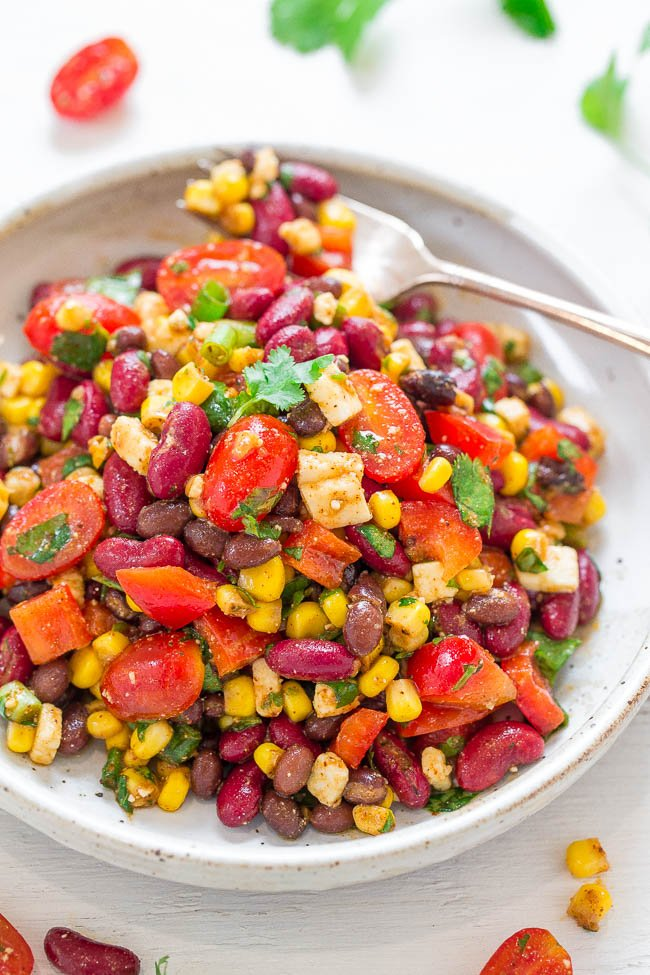 Mexican bean salad with corn on a white plate with fork