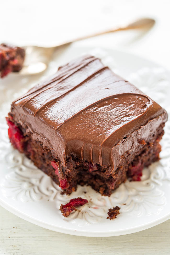 slice of Triple Chocolate Cherry Cake on white plate with bite missing