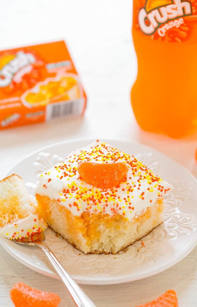 Slice of Orange Crush Poke Cake with bite taken out