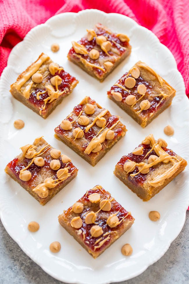 PB & J Bars - Super soft peanut butter bars topped with strawberry jelly, peanut butter chips, and a peanut butter drizzle!! Fast, EASY, and they'll be your new FAVORITE way to eat PB & J!!
