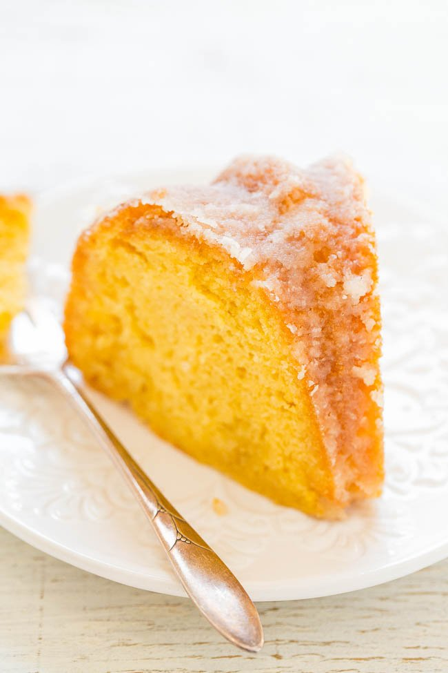 a slice of rum soaked cake on a white plate with a fork