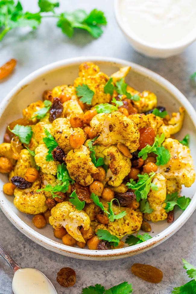 Roasted Curried Cauliflower and Chickpea Salad - An EASY, healthy, lettuce-less salad with roasted curried cauliflower and chickpeas as the STARS!! Topped with raisins, pistachios, cilantro, and a DELISH tangy Greek yogurt dressing!!