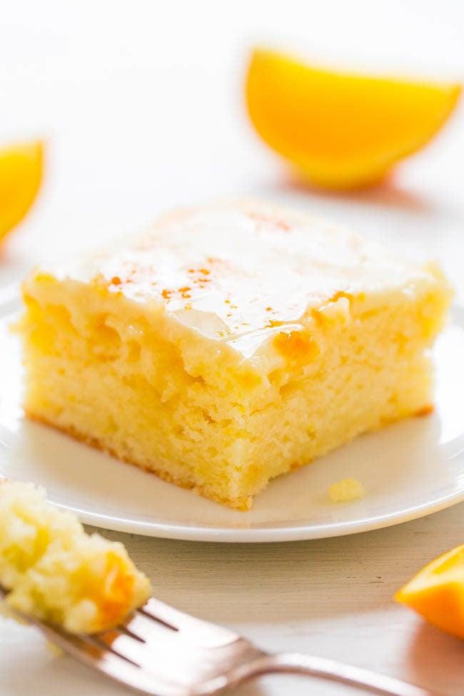 Slice of Orange Poke Cake with Honey-Orange Glaze on white plate