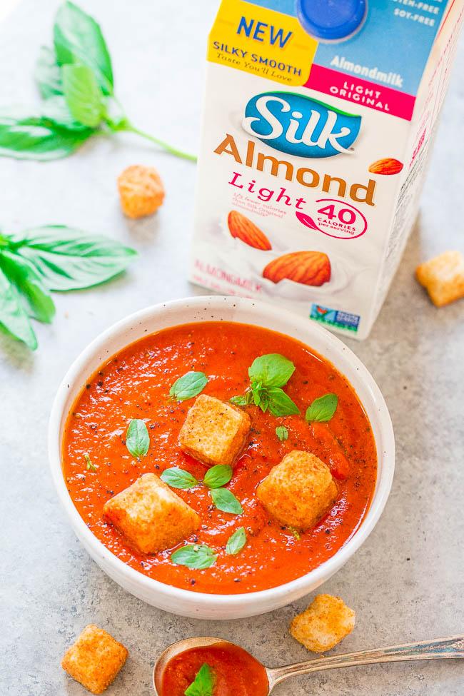 easy Tomato Basil Soup in white bowl next to carton of Silk Almond Milk
