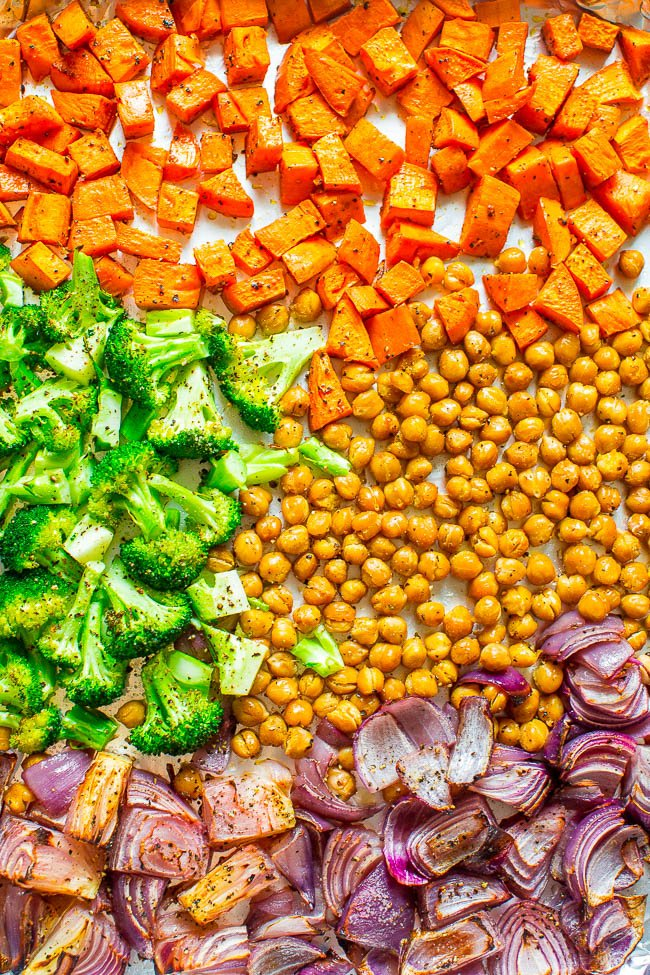 overhead view of roasted sweet potato cubes, broccoli, red onion, and chickpeas on a baking sheet
