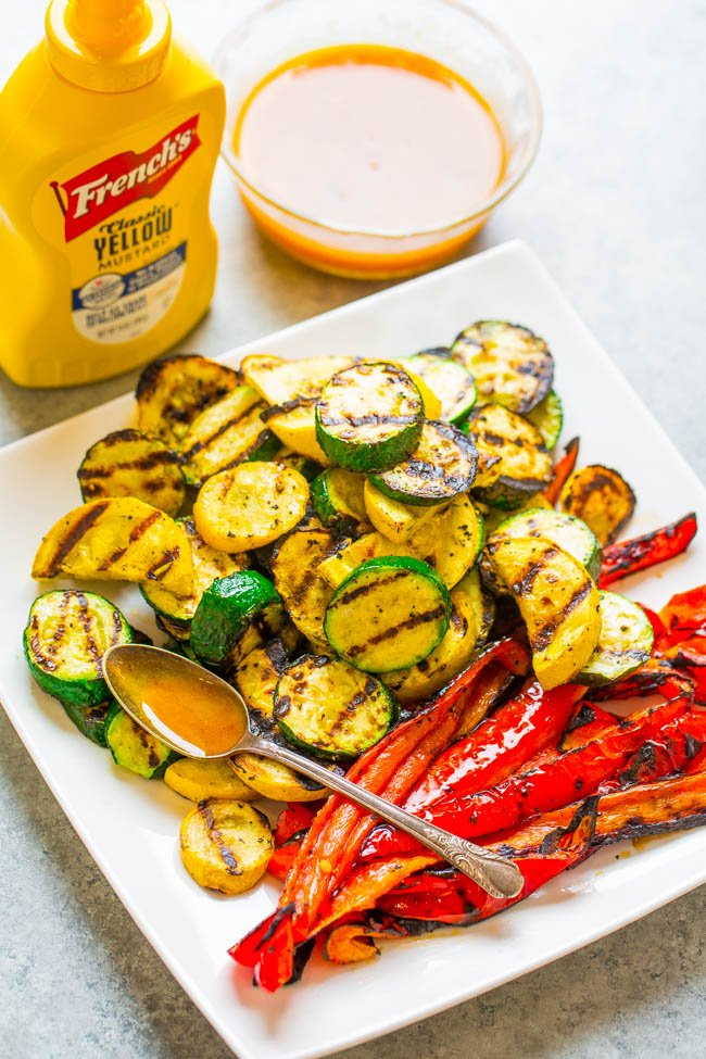 Grilled zucchini and peppers next to mustard sauce on a white plate