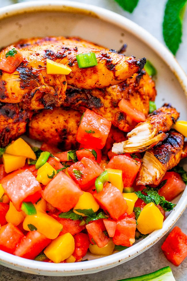 grilled chicken tenders topped with mango watermelon salsa in white dish