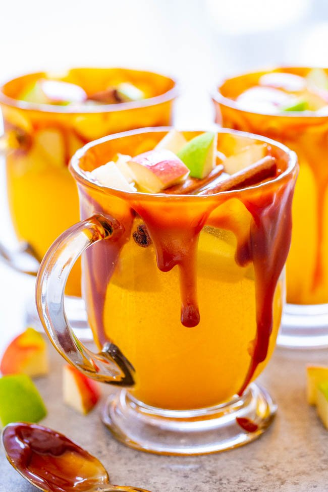 Caramel Apple Cider - Warm apple cider spiked with cinnamon, maple and almond extracts, apple chunks, and the mugs are rimmed with heavenly homemade salted caramel sauce!! FAST, EASY, and so DELICIOUS!!