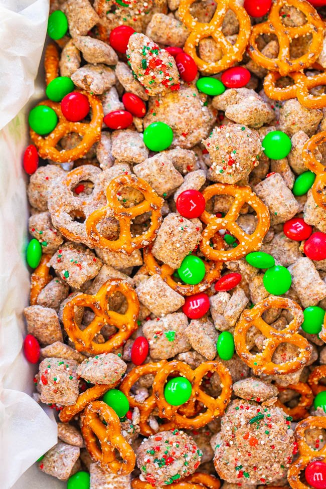 Reindeer Chow - A holiday twist on classic Muddy Buddies that's EASY, ready in 15 minutes, and perfect for hostess gifts or cookie exchanges!! Chex, chocolate, peanut butter, pretzels, M&Ms, and sprinkles make this dessert snack mix totally IRRESISTIBLE!!
