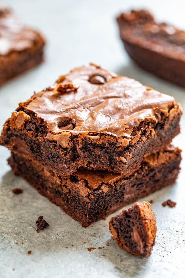 stack of two chocolate chip brownies. the top brownie has a bite missing.