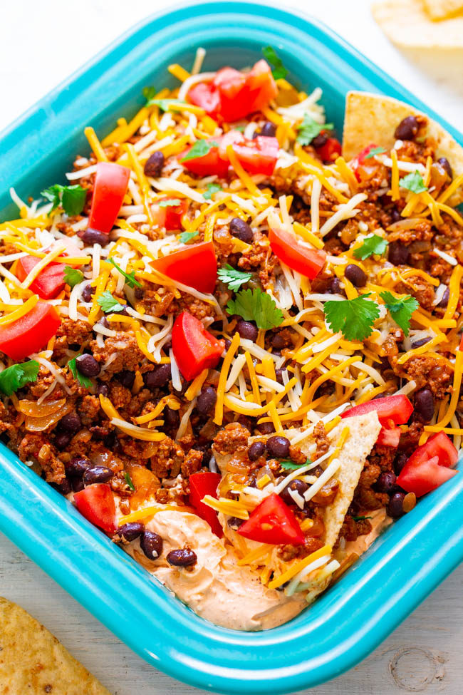 Overhead shot of Layered Beef Taco Dip in a blue dish