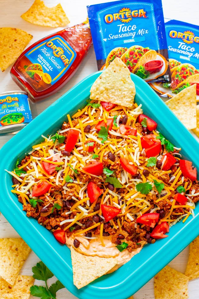 overhead shot of layered taco dip in a baking dish surrounded by tortilla chips and ortega products