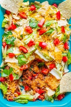 Layered Beef Taco Salad - A classic taco salad that everyone LOVES, it's EASY, and it's ready in 20 minutes!! There's ground beef, refried beans, red peppers, tortilla chips, cheese, lettuce, and tomatoes!!