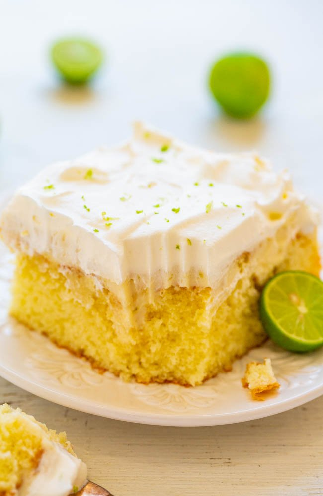 slice of key lime cake on white plate with bite missing