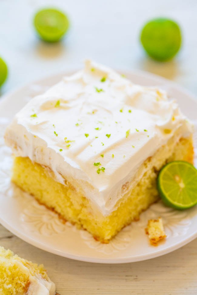 slice of key lime cake on white plate with half a lime
