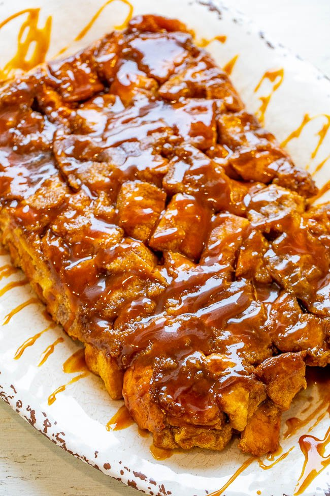 overnight french toast casserole drizzled with caramel sauce on a white platter