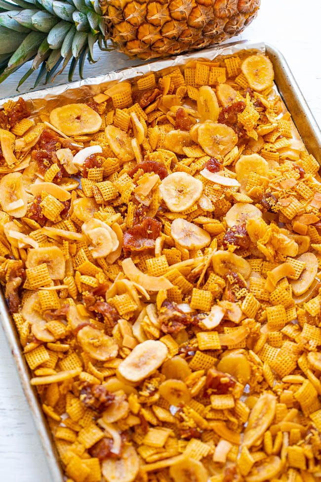Piña Colada Chex Mix on a sheet pan next to a pineapple