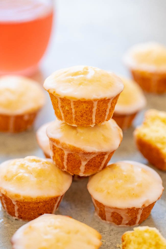 a small stack of orange muffins with glaze surrounded by other muffins