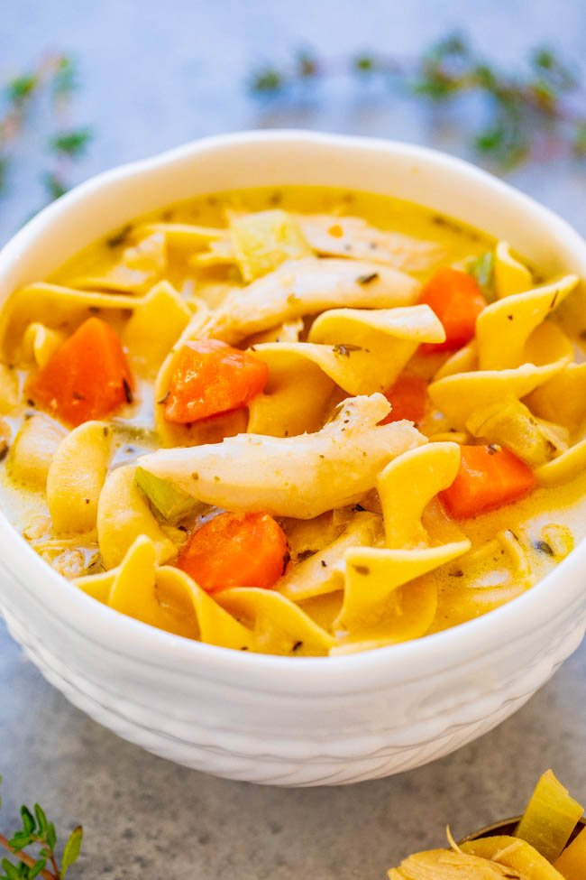 creamy, hearty chicken noodle soup in a white bowl.