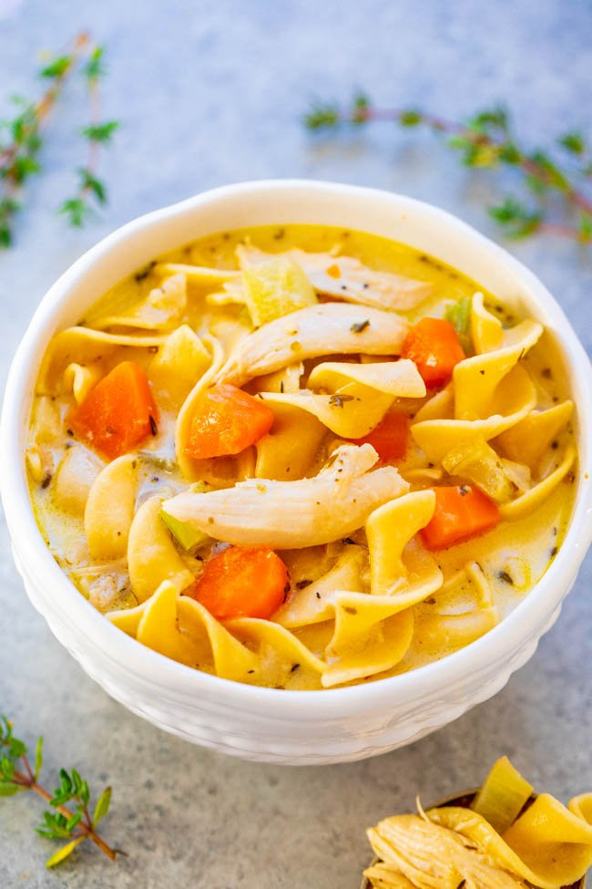 creamy chicken noodle soup in a white bowl.