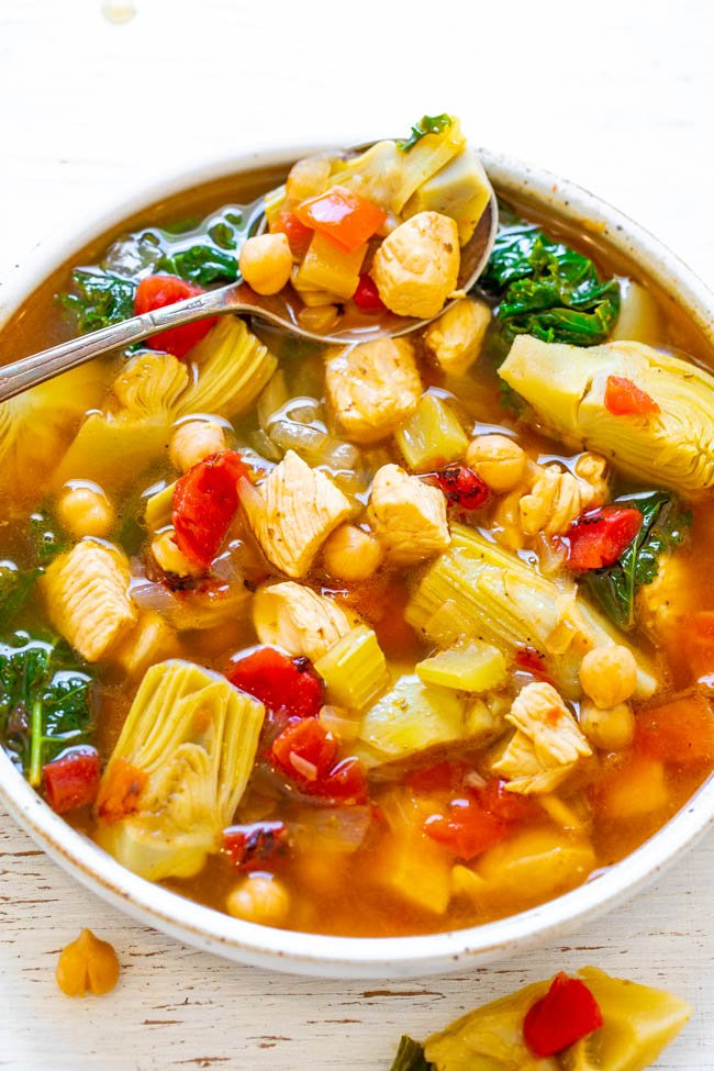 a bowl of chicken Mediterranean soup with a spoon resting on the side