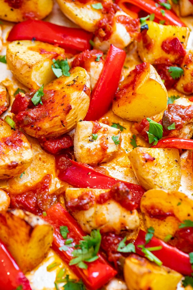 close up of potatoes, chicken and salsa on a sheet pan