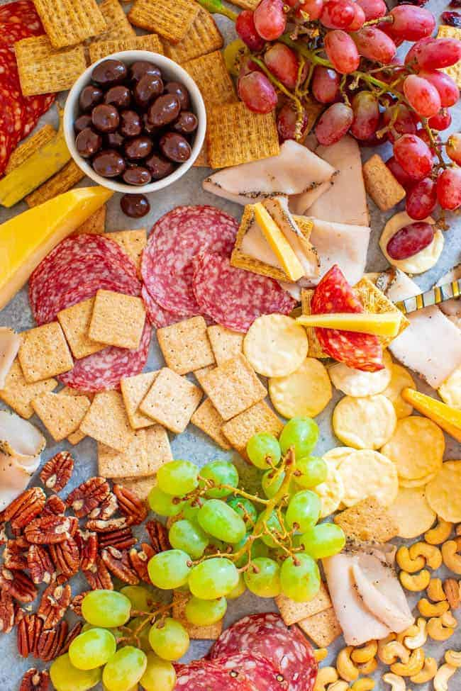 Girls Night Charcuterie Board - A SALTY-SWEET mix of meats, cheeses, fruit, chocolate almonds,Triscuits, Wheat Thins, GOOD THiNS, and more for your next GIRLS-NIGHT-IN!! There's something for everyone on this EASY-TO-ASSEMBLE board!!